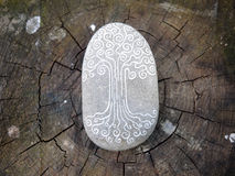 Tree of Life. A tree of life image painted on a stone. The stone is on a trunk stock photos