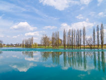 Trees and clouds reflecting on the river royalty free stock photos