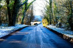 Tree lined country lane going downhill, aspalt patches on the ro. A tree lined country lane with going downhill, aspalt patches on the road, a layer of white Stock Photo