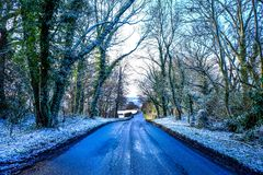 A tree lined country lane going downhill, aspalt patches on the. A tree lined country lane with going downhill, aspalt patches on the road, a layer of white snow Royalty Free Stock Images