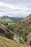 Tree lined hills and running creek in Peak District National Park, United Kingdom. Hills in background with clouds above. stock image