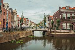 Tree-lined long canal with small bridge, brick houses on its bank and cloudy day at Gouda. Very popular day trip destination, is famous for its tasty Gouda stock images
