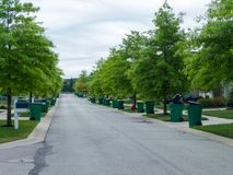 Tree lined urban street with dustbins ready stock photo