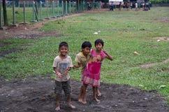 Tree local kids having fun on a field in Mrauk U, Myanmar stock photography