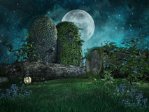 Tree logs and ivy. Night scenery with tree logs, ivy, stones, and flowers Stock Image