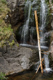 Tree logs jammed into small waterfall. Pine tree logs jammed into a small mountain stream with waterfall Royalty Free Stock Photos