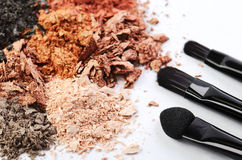 Tree makeup brushes and crumbled eyeshadows of different colors Royalty Free Stock Images