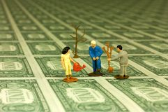 Tree nursery. Miniature figures of a woman and two men planting trees on a field of one dollar bills. With space for copy royalty free stock images