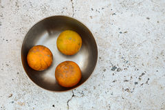 Tree oranges in stainless steel bowl. On white stone table royalty free stock photo