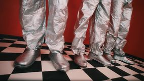 Tree pair of feet in silver galoshes and pants stomp on checkered tiled floor. Tree pair of feet in silver galoshes and tin foil pants stomp on checkered tiled stock video