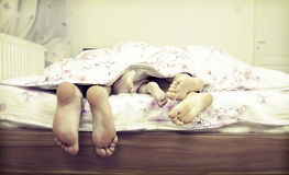 Tree pairs of legs in the bed. Tree pairs of legs - the happy family in bed:  father, mother and baby Royalty Free Stock Photos