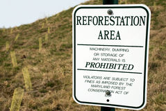 Tree Planting. Area in a new residential development set aside for reforestation. Sign prohibits machinery, dumping, and storage Royalty Free Stock Photos