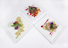 Tree plates of fine dining meal. Niceley decorated fine dining meals Stock Photos