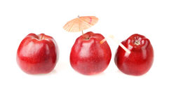 Tree red apples for fresh juice. Two fresh red apples and one apple with cocktail tube and umbrella Royalty Free Stock Photos