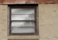 Tree reflection in window of stucco wall. Window panes reflect trees in the distance.  Wall is stucco and window is wooden Stock Image