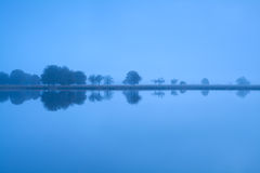 Tree reflections in lake water during misty morning Royalty Free Stock Photos