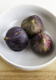 Three ripe figs in the ceramic bowl Royalty Free Stock Image