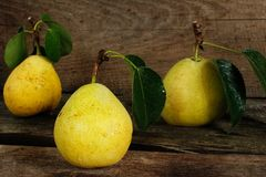 Three pears with leaves on a wooden surface Royalty Free Stock Image