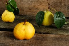 Three pears with leaves on a wooden surface Royalty Free Stock Photos