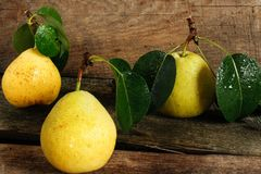 Three pears with leaves on a wooden surface Stock Photography