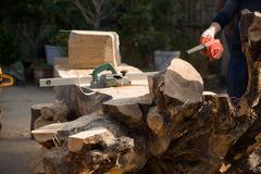 Tree-root carving. A skilled worker carved a huge root stock photography