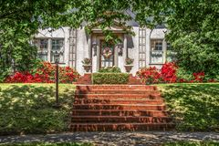 Tree shaded dappled sidewalk and sloped lawn in front of upscale stucco house with wreath and azaleas and brick steps - beautiful royalty free stock photos