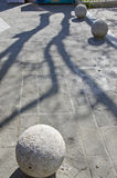 Tree shadow on street pavement with round decorative stone sphere Stock Photo