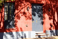 Tree shadows on red house facade in Argentina. The front of a red-painted house in Argentina is shadowed with the outlines of leafy trees. Two steps lead up to Royalty Free Stock Image
