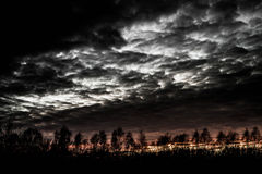 Tree silhouettes at sunset with dramatic clouds and sky Royalty Free Stock Photography