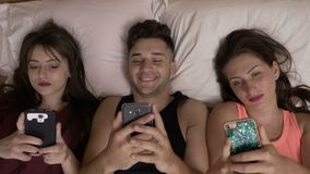 Tree teen friends in bed spending time browsing internet on their smartphones technology addiction. Tree teen friends relaxed in bed spending time browsing stock video