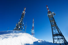Tree telecommunication towers on snowy mountain Stock Image