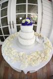 Tree tier Wedding Cake at the beach house. Three tier wedding cake with blue and white flower topper. On white round table. Beach house doors in background Royalty Free Stock Photography