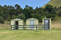 Tree tiny Public Bathrooms. Three tiny green public bathrooms under grass covered hillock royalty free stock image