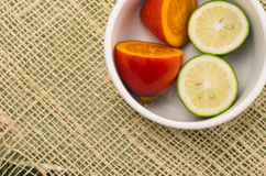Tree tomato and limes cut in halfs inside white Royalty Free Stock Photo