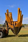 Tree transplanting spade. The mounted spade, jaws, and bucket are part of a tree removal and transplanting machine dropping the tree into the hole and removing Stock Image