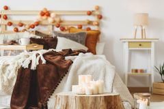 Tree trunk in the room. With many candles and a double bed in the background Royalty Free Stock Image