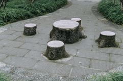 Park patio with tree trunk shaped table and chairs royalty free stock photos
