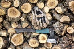 Tree trunks stacked with axe and gloves. Pile of tree trunks sawn ready for fireplace in the winter months. Chopped with axe and safety gloves Royalty Free Stock Photo