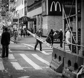 Candid image of a construction worker seen carrying tree trunks across from a fast food restaurant in New York. stock photos
