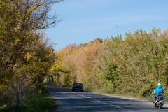 Tree tunnel with car and motorcycle. Autumn landscape royalty free stock photos