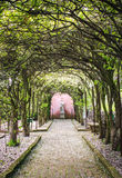 Tree tunnel with walkway and statue Stock Photo