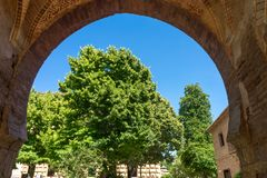 Tree viewed through an Arch at the Alhambra Palace in Granada, S. Pain, Europe on a bright sunny day with blue sky Royalty Free Stock Image
