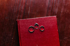 Tree wedding rings on red book with rustic wooden background Royalty Free Stock Photography