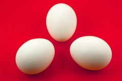Tree white eggs on red background. Clipping path for easy change background Royalty Free Stock Image