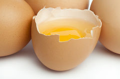 Tree whole eggs and another broken in half raw egg Stock Image