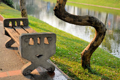 Tree winding around a bench. A tree grew around a bench along a river Royalty Free Stock Image