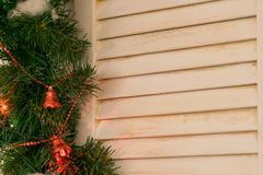 A tree window framed by Christmas tree branches with Christmas decorations. stock images