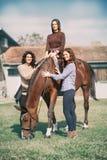 Tree woman enjoy with tame a beautiful horse. Tree farmers women enjoy with tame a beautiful horse stock photos