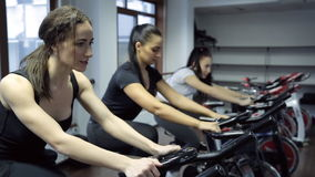 Tree women do exercises on exercise bike in fitness center. Young slim woman in black training suit, small earnings, yellow hair elastic, brunette with stock video