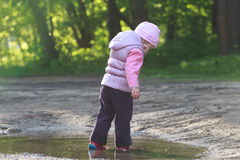 Tree years old girl exploring summer puddle in red gums Royalty Free Stock Image